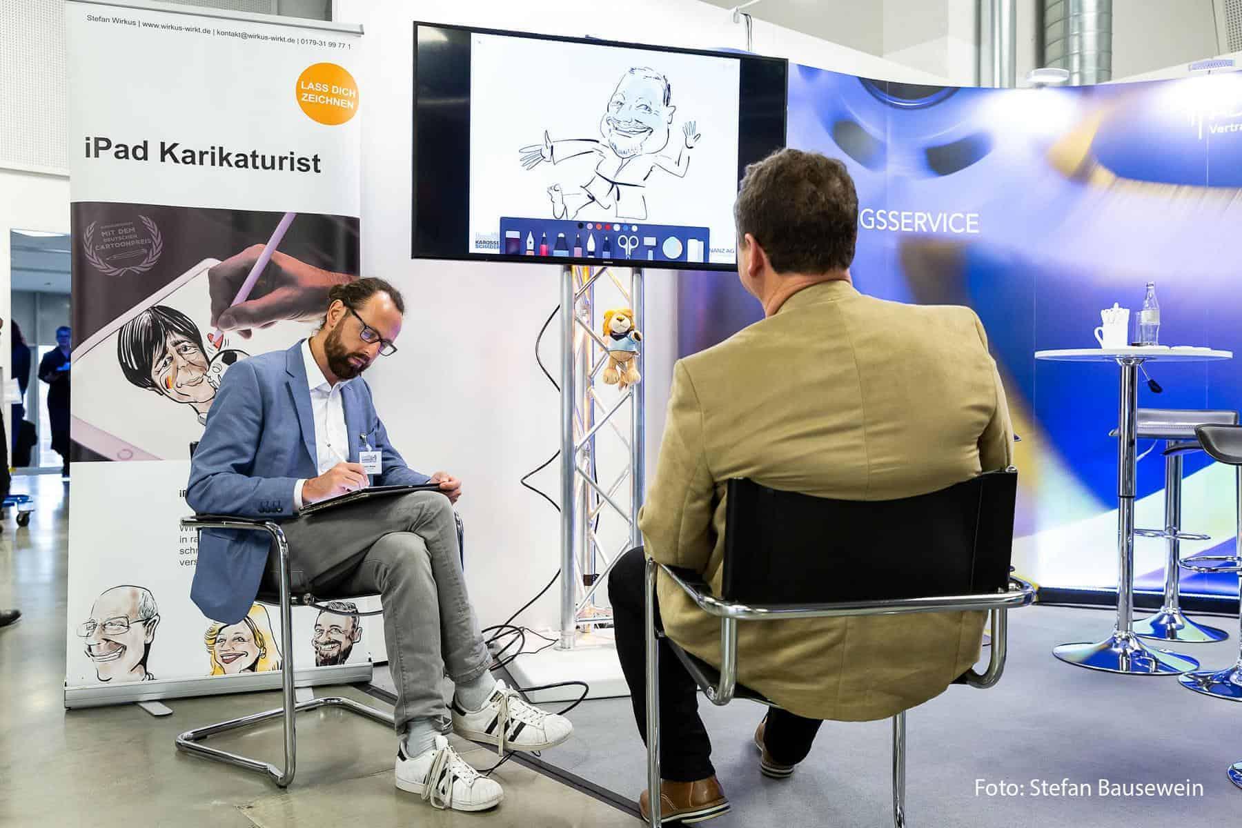 Ein Karikaturist am Stand der ADELTA.FINANZ AG auf den Würzburger Karosserie- und Schadenstagen 2018.